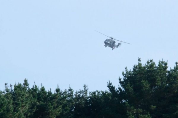 NH90 helicopter flies low over Waikawa Beach village.