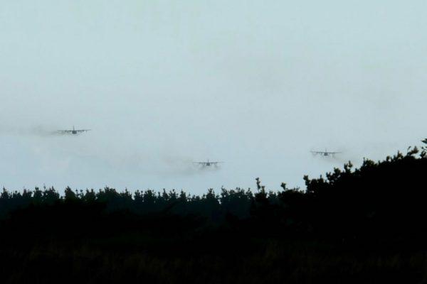 Three low flying Hercules aircraft.
