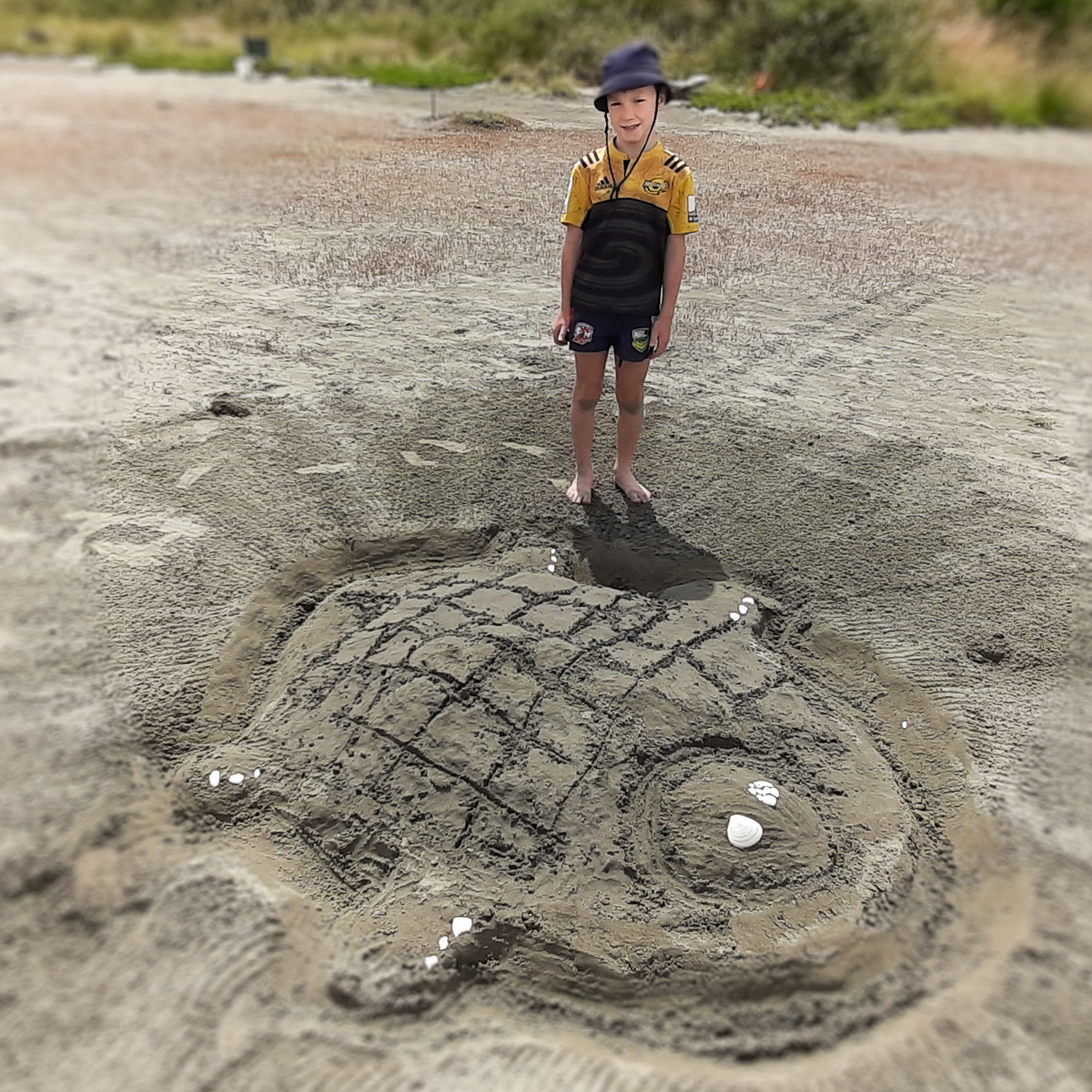 Child beside sand turtle.