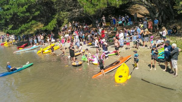 Kayaks, canoes and loads of people by the river.