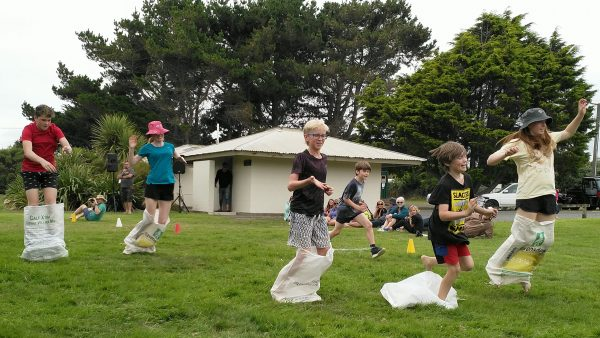 Children with legs in sacks, racing.