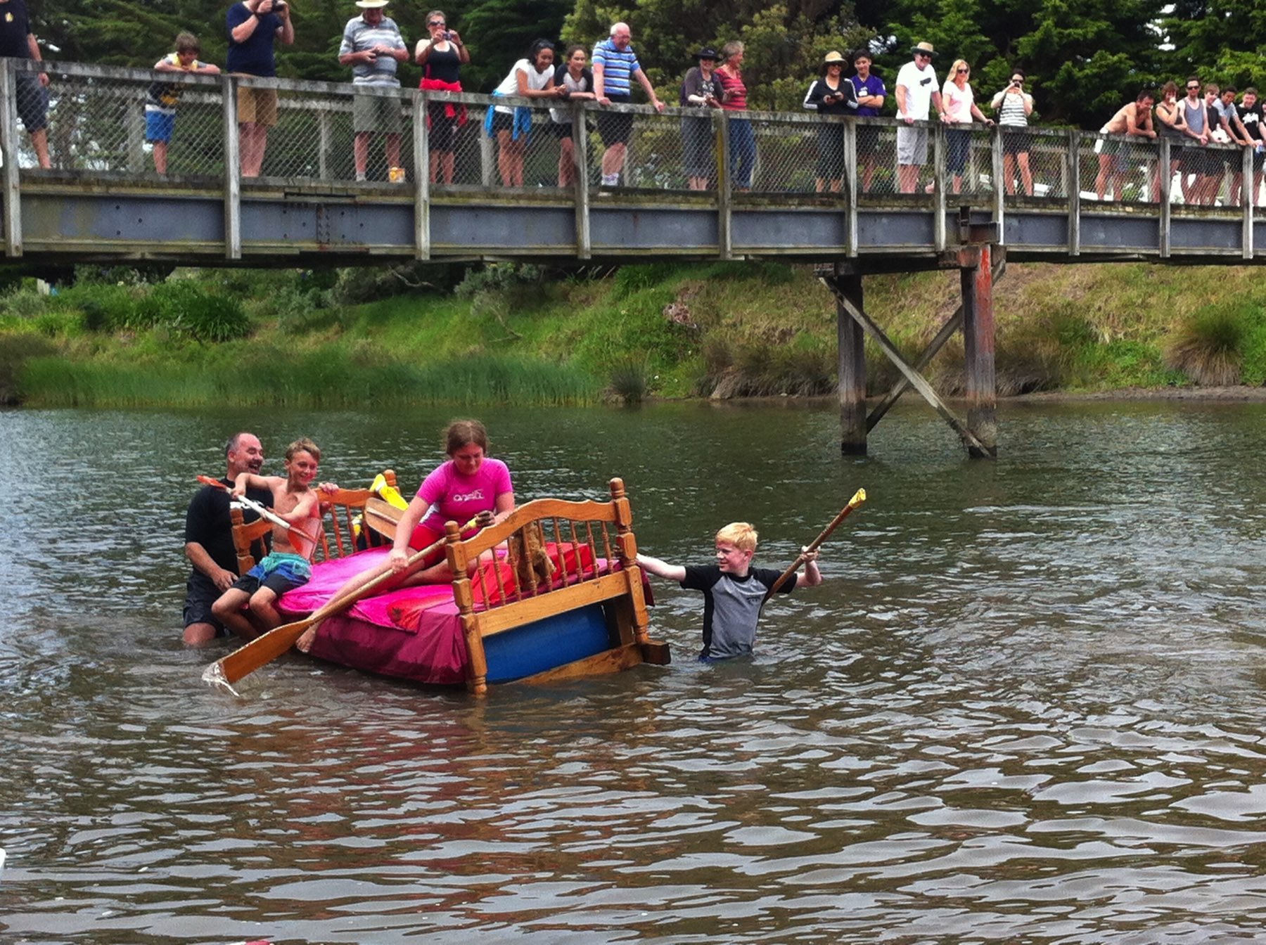 A bed-shaped boat in the river, with many onlookers.