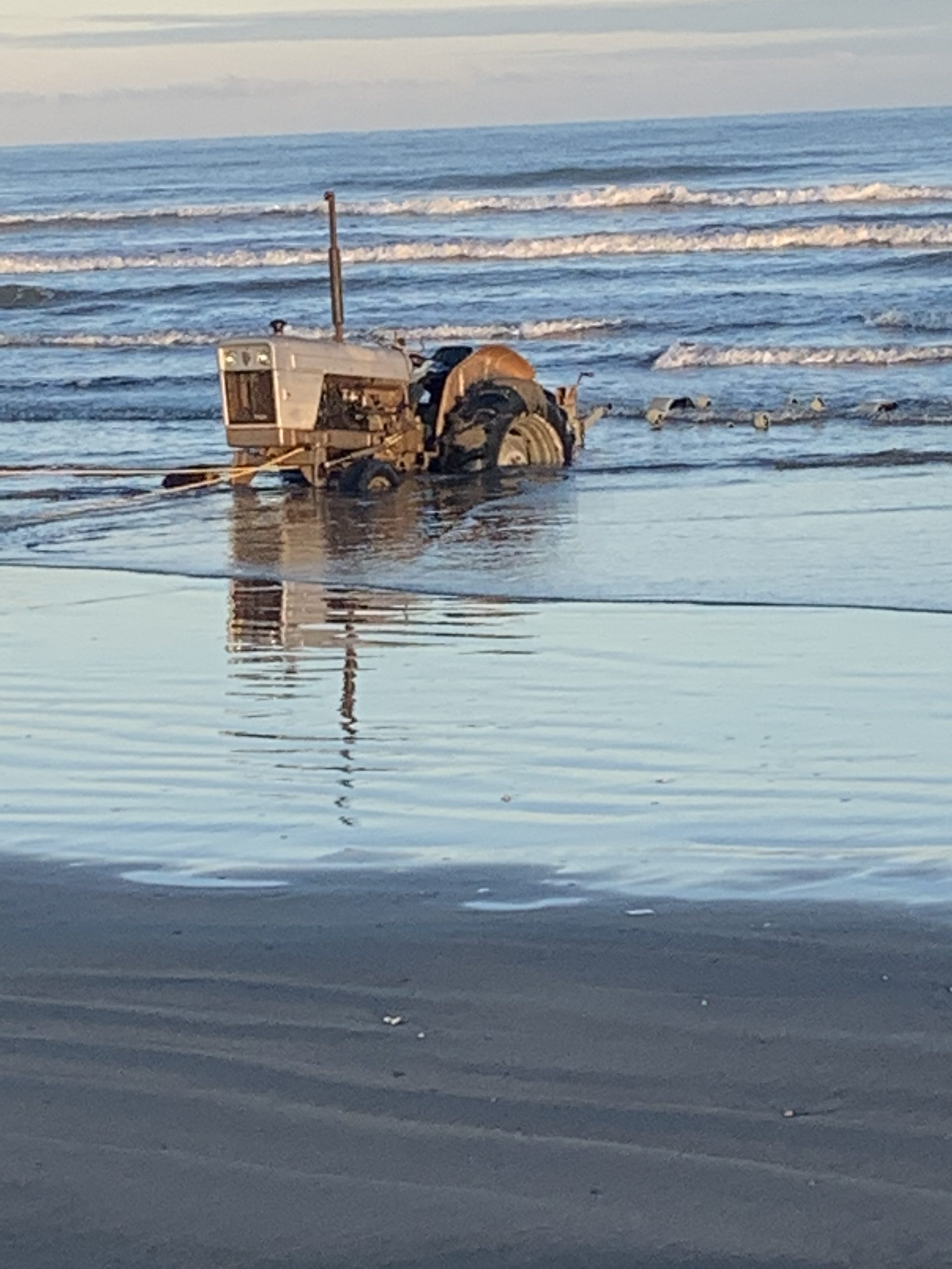 A tractor stuck in the sand and sea.